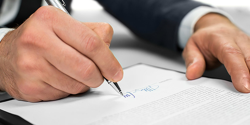 Man works with papers. The document needs a signature. Signing a letter. Official letter to a partner.